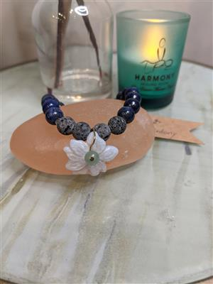 """<p>&nbsp;</p> <p>This gorgeous Lapis Lazuli and lava stone bracelet is accentuated by a carved blue chalcedony flower charm. These blue colored stones are soothing and deeply calming. The aromatherapy lava stone is uncoated, giving it a more natural feel.</p> <p>&nbsp;</p> <p><strong>How to use:</strong></p> <p>Add several drops of essential oil to the porous black lava stone for a beautiful and portable diffuser. Scents can last several days to weeks.</p> <p><strong>Sizing:</strong></p> <p>Bracelet should fit a medium wrist .The average Medium sized bracelet is approximately 8-9 inches.</p> <p>Each bracelet is unique and currently we only have 1 of each in stock, however different sizes or quantities can be made on request.</p> <p><strong>Quality:</strong>We primarily source our materials through US- based stores and small businesses. We choose almost exclusively un-dyed gemstones and natural materials as much as possible and will notate in the listing if a stone has been dyed on altered to the best of our knowledge.</p> <p><strong>Shipping:</strong>We batch ship 1-2 times per week depending on sales volume. If you need your items in a hurry please send us a message at info@harmonymassageli.com</p> <p><img src=""""https://cdn.bookingtimes.com/Common/LoadImage.ashx?Id=24805&v=1"""" width=""""509"""" height=""""679"""" style=""""display: block; margin-left: auto; margin-right: auto;"""" /></p>"""