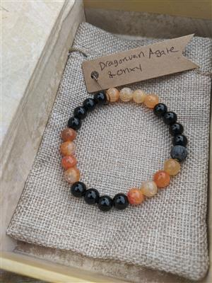 <p>Beautiful and bright cracked orange Agate and Deep Black Onyx make a unique combination in this diffuser bracelet. One unwaxed lava stone makes the center focal point for the bracelet and can hold essential oils.</p> <p><strong>How to use:</strong>Add several drops of essential oil to the porous Black lava stone for a beautiful and portable diffuser. Scents can last several days to weeks. All bracelets are made with Stretchy material that has some give for taking it on and off. Rolling the bracelet onto the wrist will help preserve the stretch cord and keep it from being overstretched too quickly.</p> <p>&nbsp;</p> <p><strong>Sizing:</strong>Bracelet should Medium to Large wrist about 9 inches .The average Medium sized bracelet is approximately 8-9 inches.</p> <p>Each bracelet is unique and currently we only have 1 of each in stock, however different sizes or quantities can be made on request.</p> <p>&nbsp;</p> <p><strong>Quality:</strong>We primarily source our materials through US- based stores and small businesses. We choose almost exclusively un-dyed gemstones and natural materials as much as possible and will notate in the listing if a stone has been dyed on altered to the best of our knowledge.</p> <p><strong>Shipping:</strong>We batch ship 1-2 times per week depending on sales volume. If you need your items in a hurry please send us a message at info@harmonymassageli.com</p>